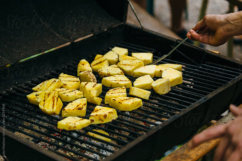 Man Tending To Sliced Pineapple Cooking Over BBQ Grill by Luke Mattson for Stocksy United