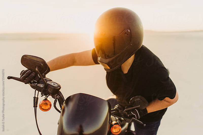 Biker getting on motorcycle by Isaiah & Taylor Photography for Stocksy United