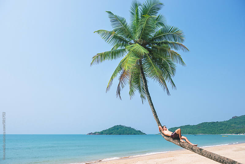Relaxed man lying on a bent coconut trunk on exotic beach  by RG&B Images for Stocksy United