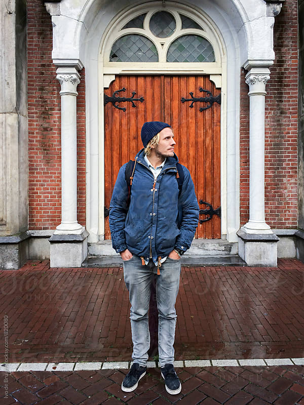 young man with beanie standing in front of the door of a church in Amsterdam by Ivo de Bruijn for Stocksy United