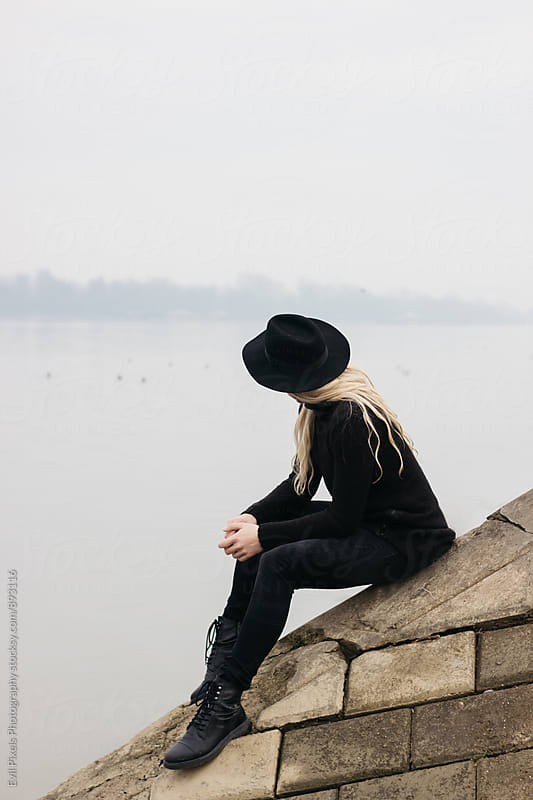 Anonymous male model with black hat and long hair sitting near river by Evil Pixels Photography for Stocksy United