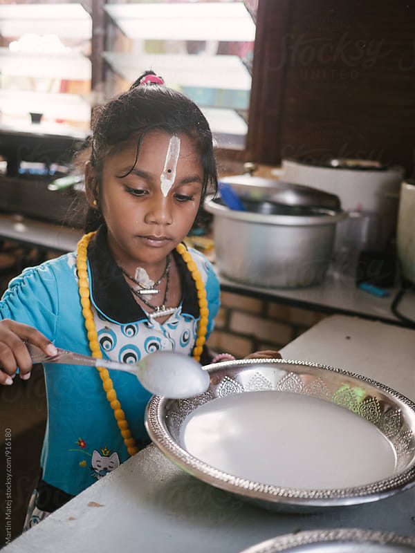 Adorable Indian Girl helps with cooking by Martin Matej for Stocksy United