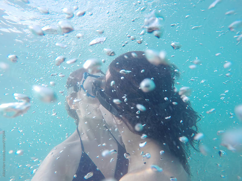 Couple kissing underwater surrouded by numerous bubbles by Alice Nerr for Stocksy United