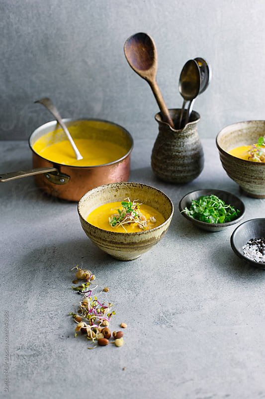 Carrot soup: Servings of carrot soup in a concrete background. by Darren Muir for Stocksy United