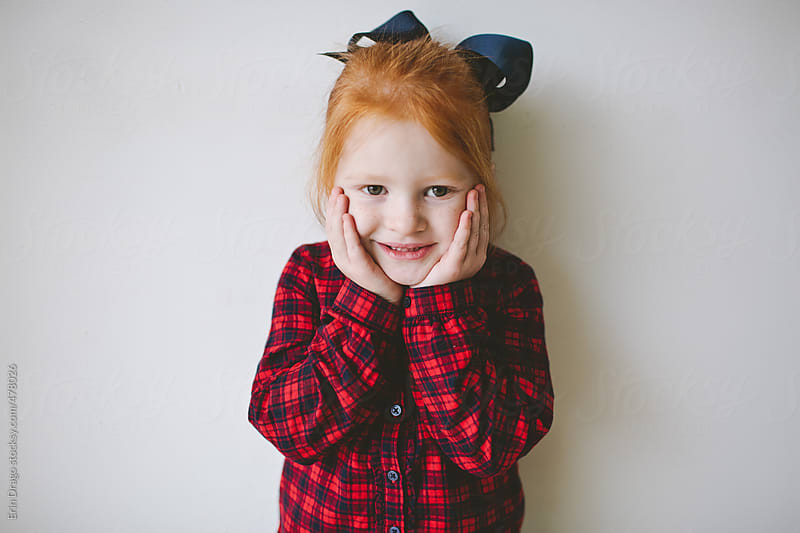 little redheaded girl with hands on her face by Erin Drago for Stocksy United