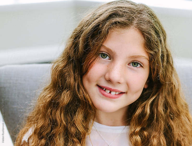 Girl with long curly hair, smiling.  by Helen Rushbrook for Stocksy United
