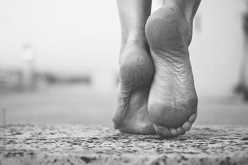 Barefoot woman stepping forward by Silvia Cipriani for Stocksy United