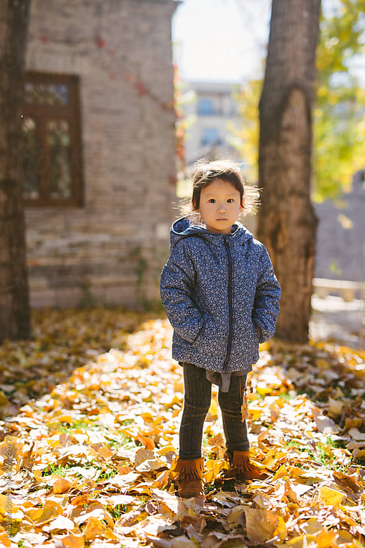 Toddler girl standing in autumn park by Maa Hoo for Stocksy United