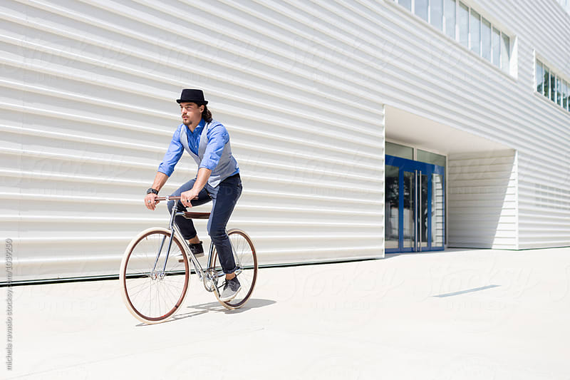 Fashionable man cycling in urban area by michela ravasio for Stocksy United