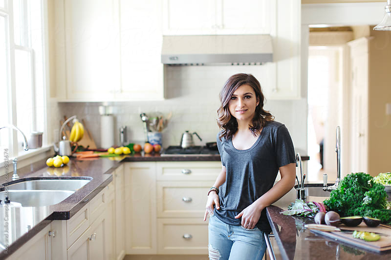 Young woman standing in kitchen looking at camera - kale on counter by Rob and Julia Campbell for Stocksy United
