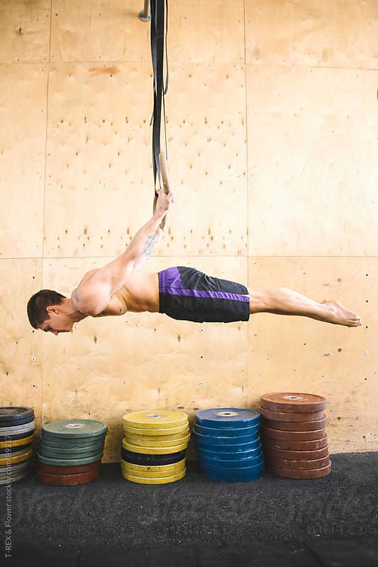 Man performing exercise on gymnastic rings by Danil Nevsky for Stocksy United