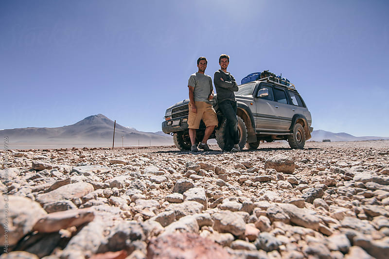 Two young friends next to a 4wd all terrain car on adventure travel on desert landscape by Alejandro Moreno de Carlos for Stocksy United