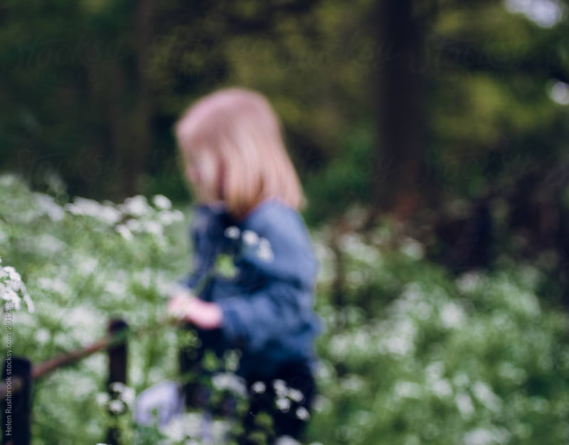 Blurry image of a little girl standing on an iron fence among cow parsley by Helen Rushbrook for Stocksy United