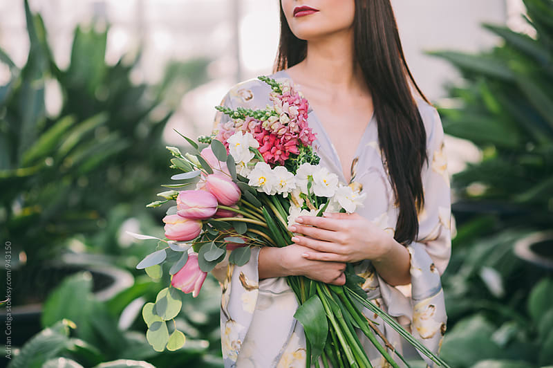 Young woman with long hair holding flowers bouquet by Adrian Cotiga for Stocksy United