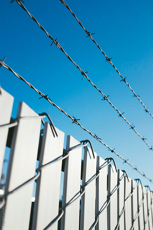 Barbed wire and chain-link fence, close up by Paul Edmondson for Stocksy United