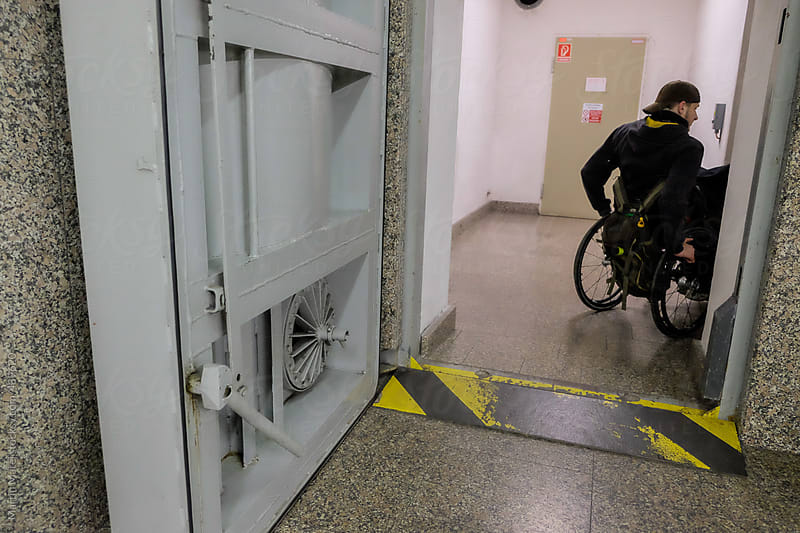 Disabled man going through the hallway by Martin Matej for Stocksy United