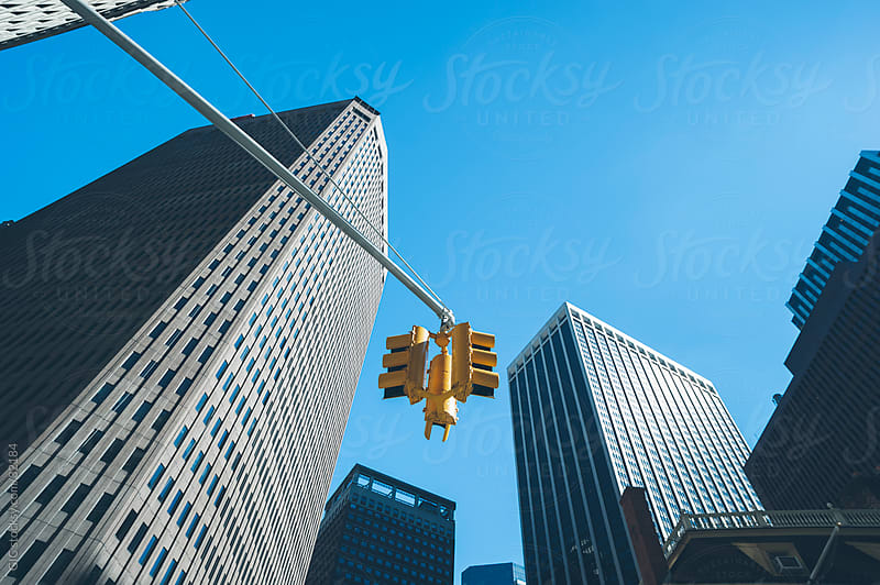 Traffic light and skyscraper in a road, New York City by Simone Becchetti for Stocksy United