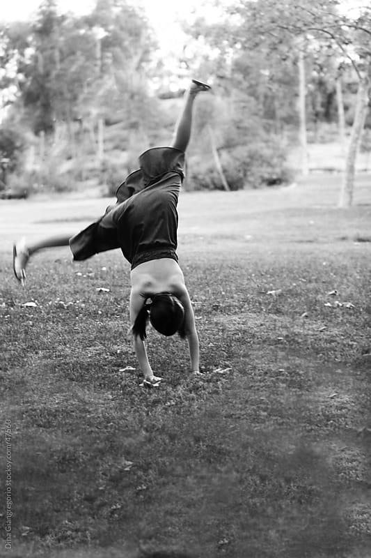 Black and white photo showing a young girl in dress , age 8-13 doing a cartwheel in a park. back view only. by Dina Giangregorio for Stocksy United