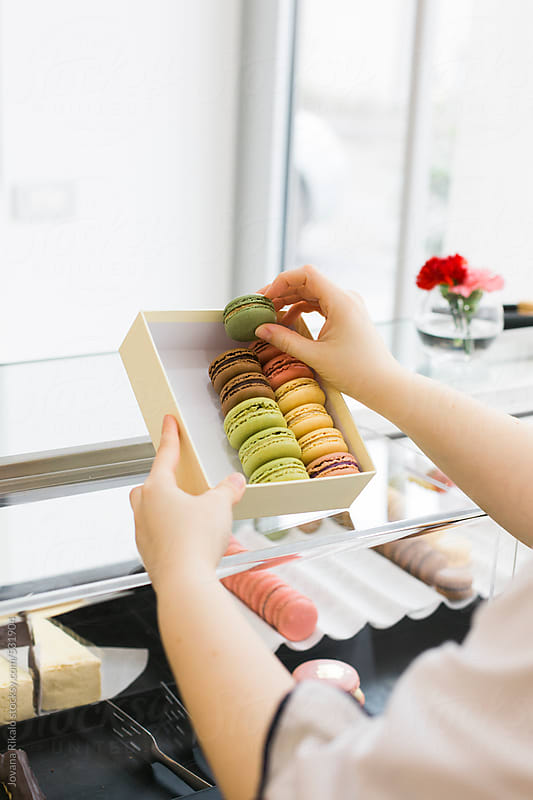 Woman selects macaroons at bakery by Jovana Rikalo for Stocksy United