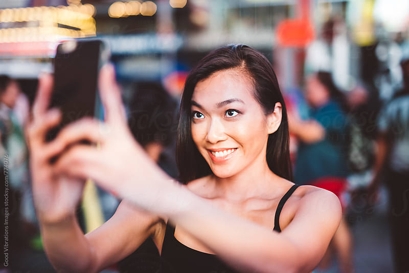 Asian woman taking a selfie in Time Square by Good Vibrations Images for Stocksy United