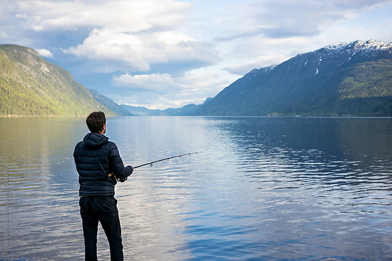 Fishing in a lake in Norway by Tristan Kwant for Stocksy United