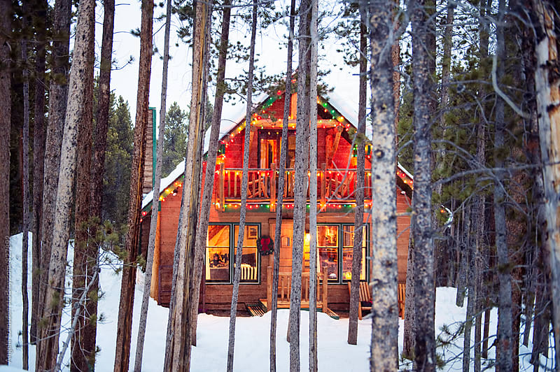 Small cabin glowing with holiday lights and inside warmth in a snow covered landsape by Angela Lumsden for Stocksy United
