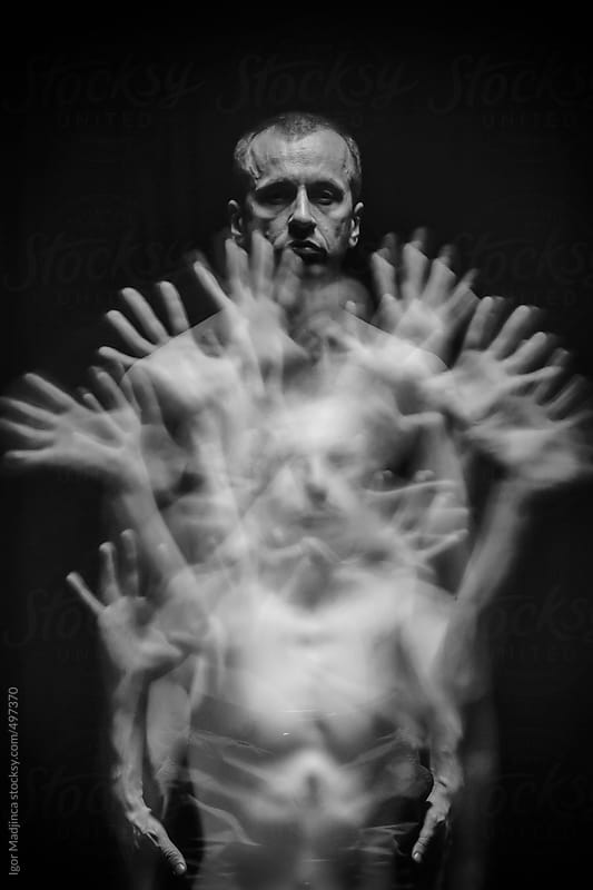 hand movements, long exposure, man,dark sun by Igor Madjinca for Stocksy United