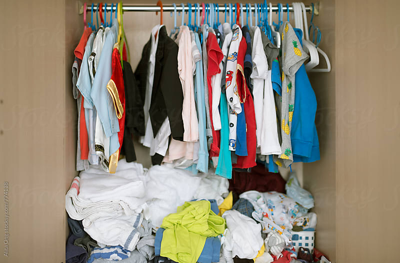 Messy kid's wardrobe BEFORE major decluttering and purging as new year resolution by Alita Ong for Stocksy United