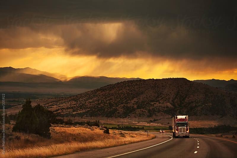 semi-truck driving in beautiful mountain scene by ryan matthew smith