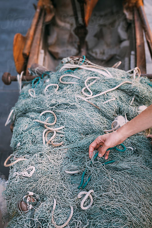 Female hand holding fisherman´s net by Maja Topcagic for Stocksy United