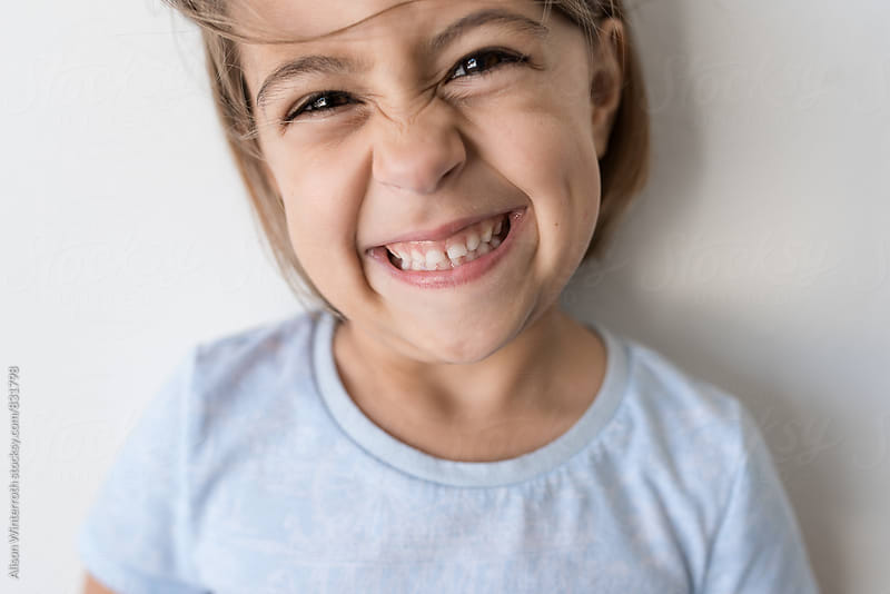 Child With Flying Hair Smiles At Camera by Alison Winterroth for Stocksy United