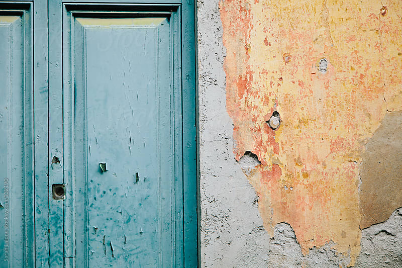 turquoise door and orange plaster wall by Sarah Lalone for Stocksy United