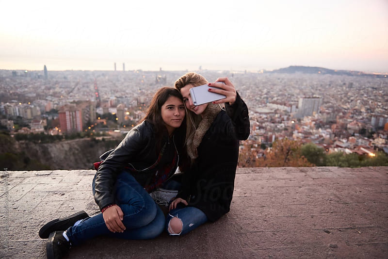 Two women taking selfie against of cityscape by Guille Faingold for Stocksy United