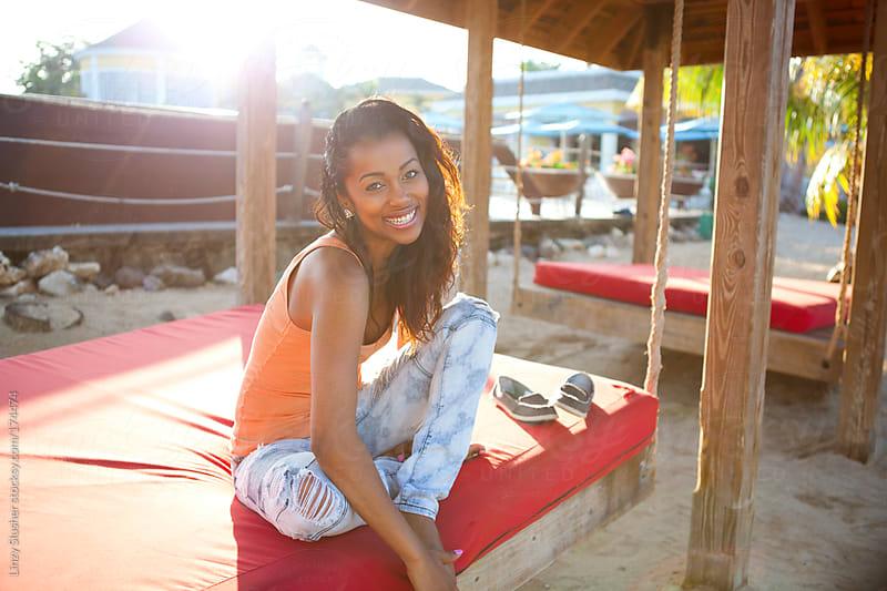 Beautiful Jamaican woman sitting on beach swing by Linzy Slusher for Stocksy United