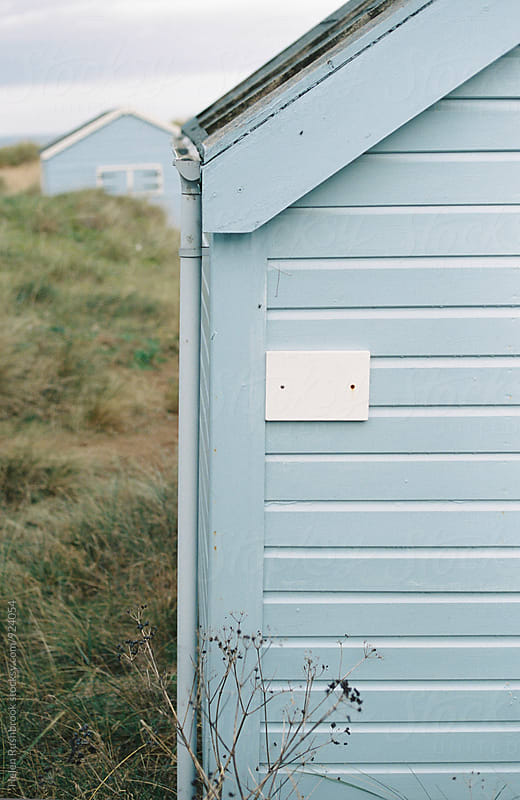 A pale blue beach hut by Helen Rushbrook for Stocksy United