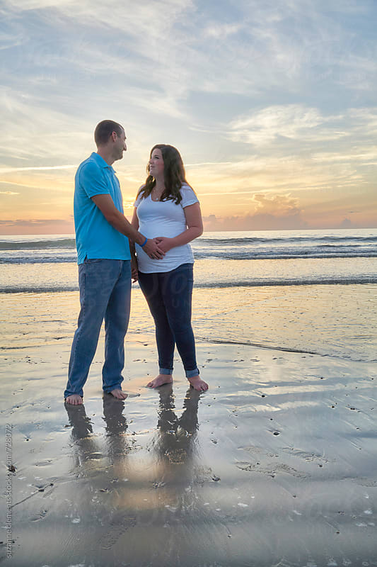 Pregnant Woman and her Husband at the Beach at Sunrise by suzanne clements for Stocksy United
