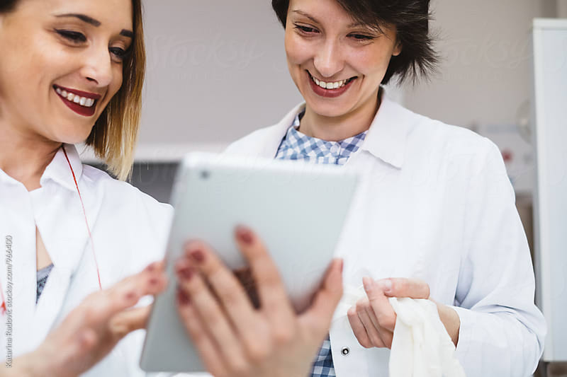 Two Female Doctors Using Tablet While Working by Katarina Radovic for Stocksy United