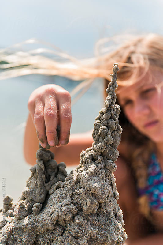 Teen Girl building Sandcastle by Raymond Forbes LLC for Stocksy United