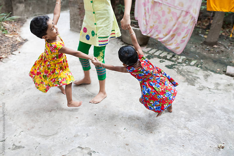 A teenager playing with twin girls by PARTHA PAL for Stocksy United