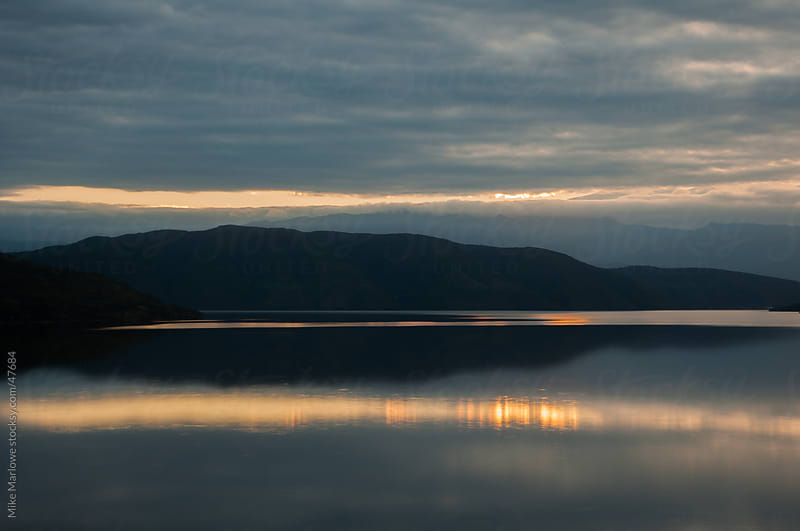 Sunset reflections in a lake with background hills by Mike Marlowe for Stocksy United