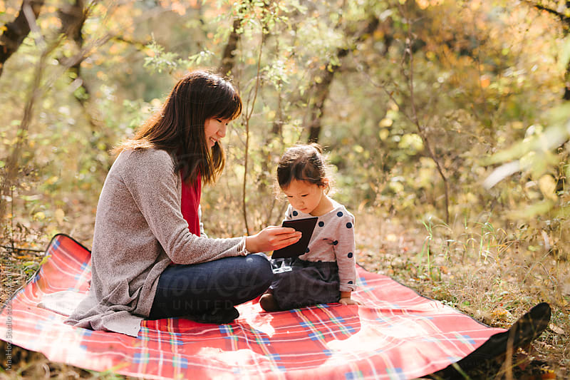 Young mother and toddler girl using digital tablet on picnic mat by Maa Hoo for Stocksy United
