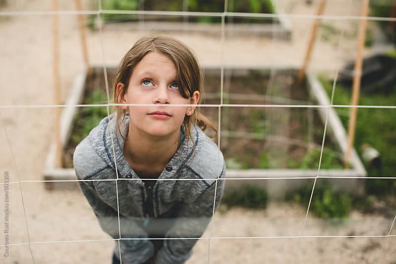 young girl looking up in the garden by Courtney Rust for Stocksy United