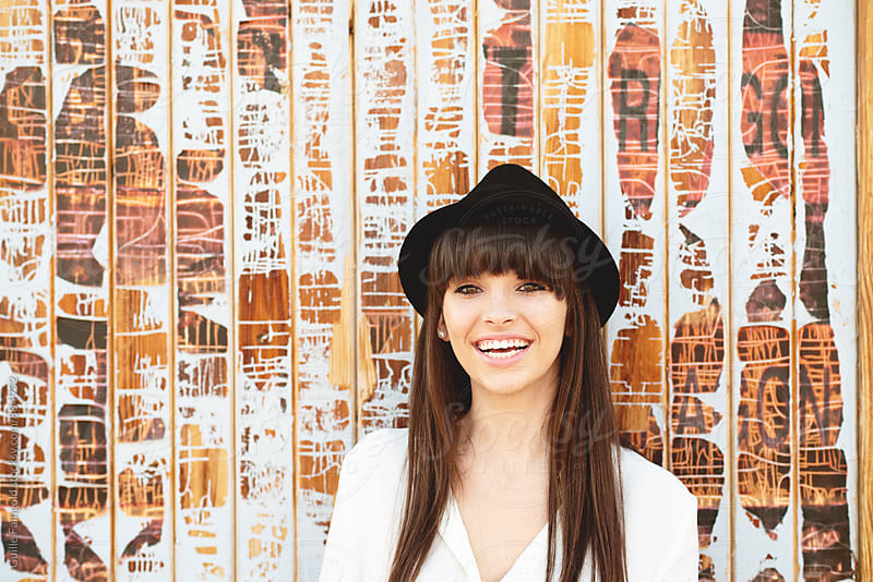 smiling young woman against old wooden wall by Guille Faingold for Stocksy United