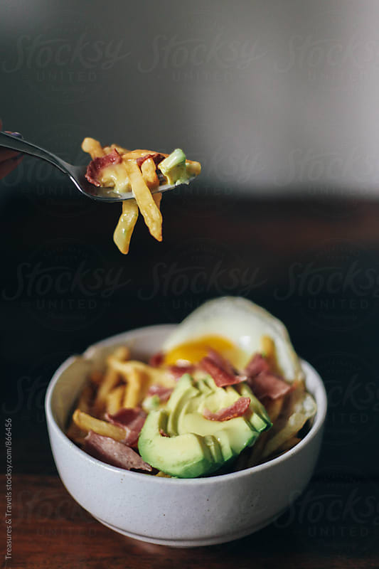 Woman eating a Breakfast Poutine by Treasures & Travels for Stocksy United