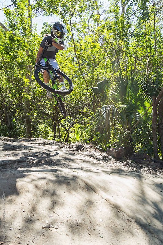 Female mountain biker catching air by Adam Nixon for Stocksy United
