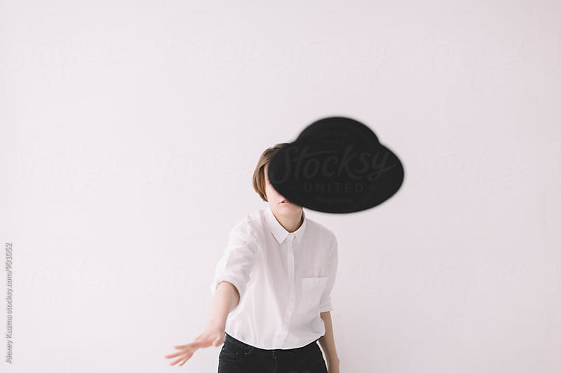 young woman throwing her hat at the camera, selective focus  by Alexey Kuzma for Stocksy United