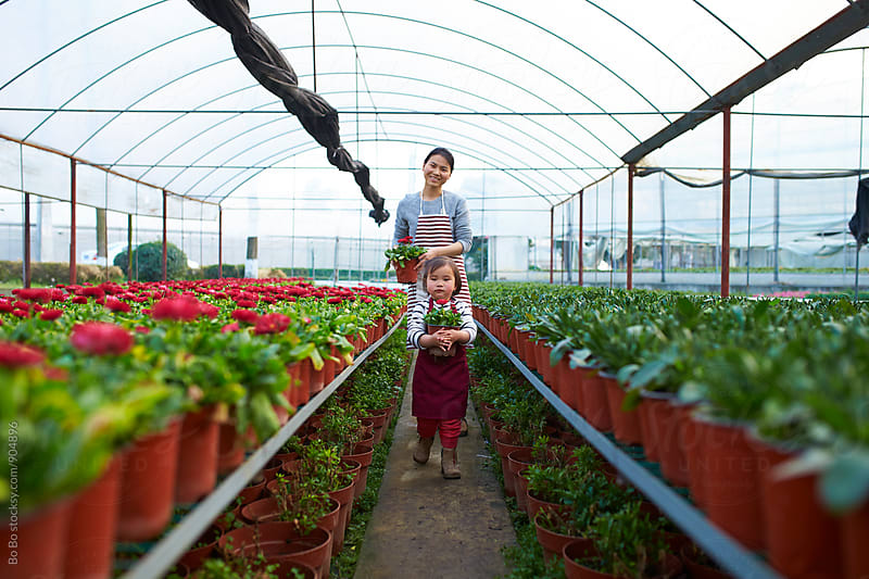 little asian girl working in the garden with her mother by Bo Bo for Stocksy United