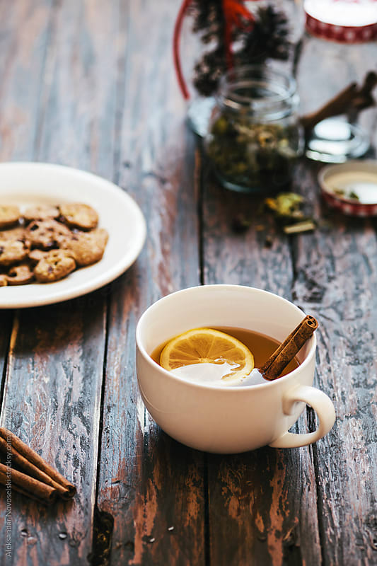 Tea with lemon slice, cinnamon sticks and cookies on a wooden table by Aleksandar Novoselski for Stocksy United