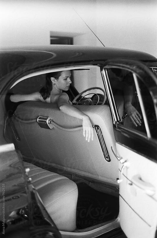 a black and white film portrait of a young beautiful woman sitting in the old car by Anna Malgina for Stocksy United