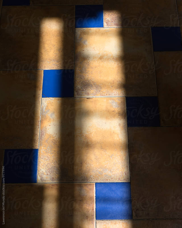 Light and shadow play on a beautifully tiled floor  by Lawrence del Mundo for Stocksy United